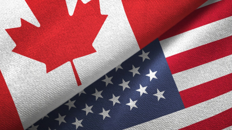 The Canadian and American flag overlapping each other